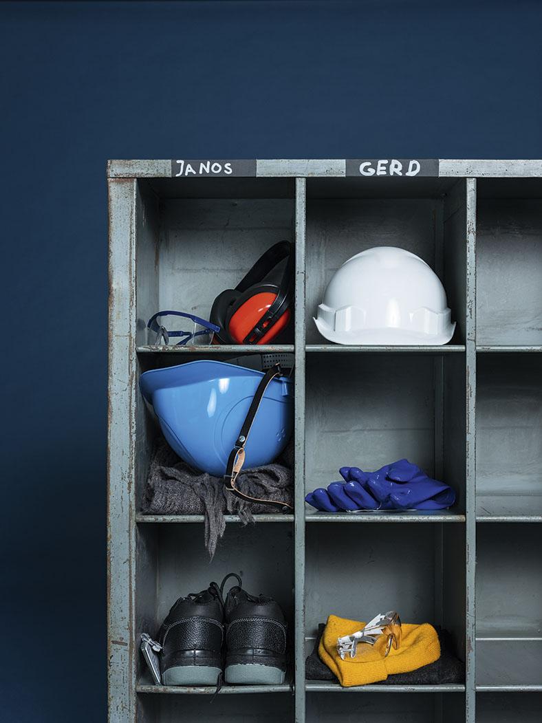 Das Foto zeigt ein Regal, in dem persönliche Schutzausrüstung untergebracht ist. Im ersten Fach (mit Namen Janos) oben links liegen Kopfhörer und eine Schutzbrille. Im Fach daneben (mit Namen Gerd) ein weißer Helm. In den Fächern darunter (Janos) ist ein blauer Helm und ein Schal reingelegt. In dem Fach daneben (Gerd) blaue Schutzhandschuhe. In einem weiteren Fach darunter ein paar schwarze Arbeitsschuhe und daneben eine gelbe Mütze.