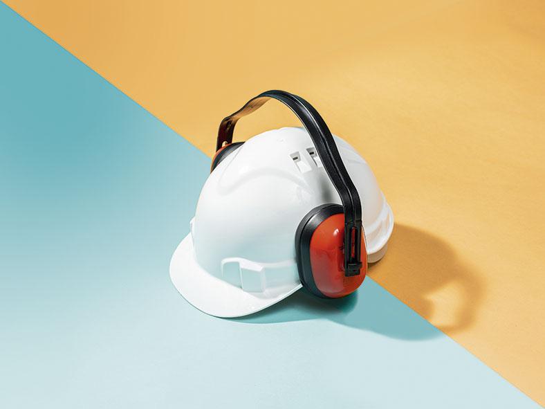 Dieses Foto zeigt einen weißen Schutzhelm auf dem Kopfhörer angebracht worden sind.