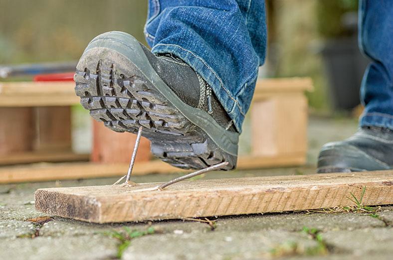 Dieses Foto zeigt einen Fuß in einem Arbeitsschuh mit groben Profil, der gerade in einen aus einem Brett herausstehenden Nagel tritt.