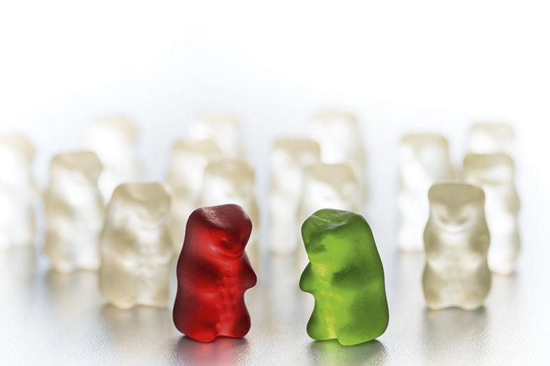 Das Bild zeigt im Vordergrund ein rotes und ein grünes Gummibärchen. Im Hintergrund sind viele farblose Gummibärchen zu erkennen.