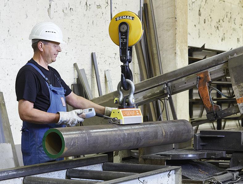 Ein Beschäftigter bedient mittels Fernbedienung eine Last mit einem Permanentmagnet zur Aufnahme eines Metallrohrs, dass sicher zu einer Metallsäge zugeführt wird.