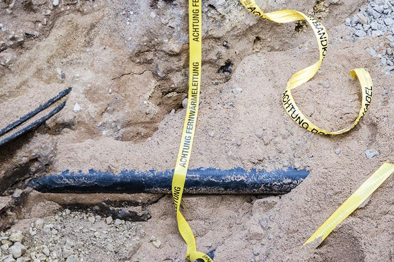 """Das Foto zeigt ein fast eingegrabenes Fernwärmeleitungsrohr. Darüber ist ein gelbes Band gelegt mit der Aufschrift """"Achtung Fernwärmeleitung""""."""