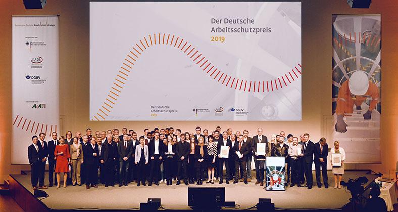 """Dieses Foto zeigt mehrere Preisträger auf einer Bühne. Im Hintergrund an der Wand ist ein großes Plakat mit dem Text """"Der Deutsche Arbeitsschutzpreis 2019""""."""