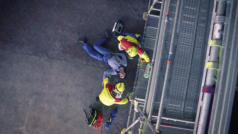 Ein Arbeiter ist von einem Gerüst gestürzt. Zwei Personen mit Schutzausrüstung kümmern sich um den Verletzten.