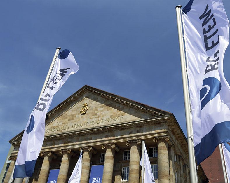 """Dieses Foto zeigt das Kongress Palais in Kassel. Im Vordergrund sind zwei Flaggen zu sehen mit der Aufschrift """"BG ETEM""""."""