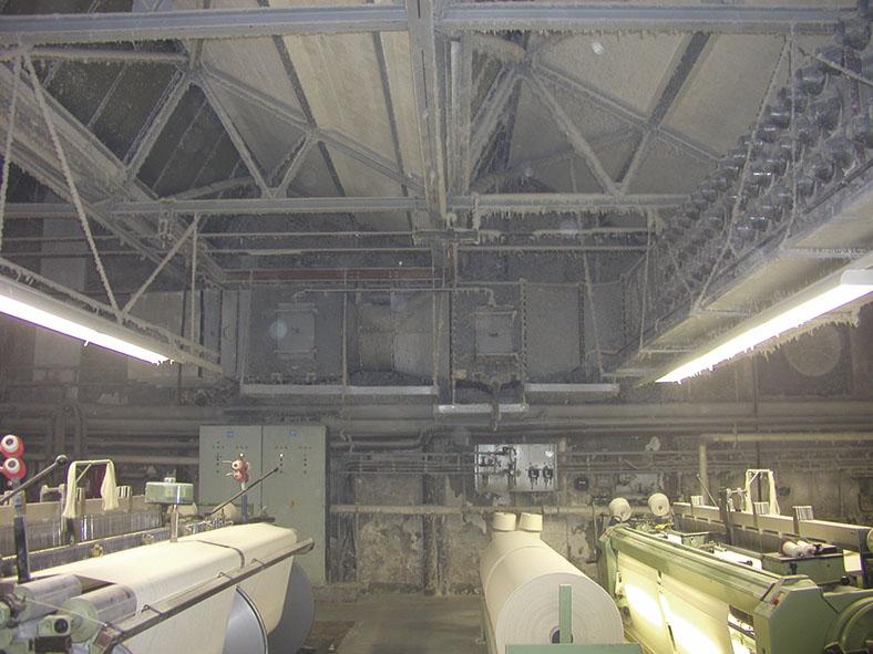 Dieses Foto zeigt einen Produktionssaal. Hier liegt ein hohes Brandrisiko vor. Durch einen geeigneten Reinigungsplan lässt sich das vermeiden.