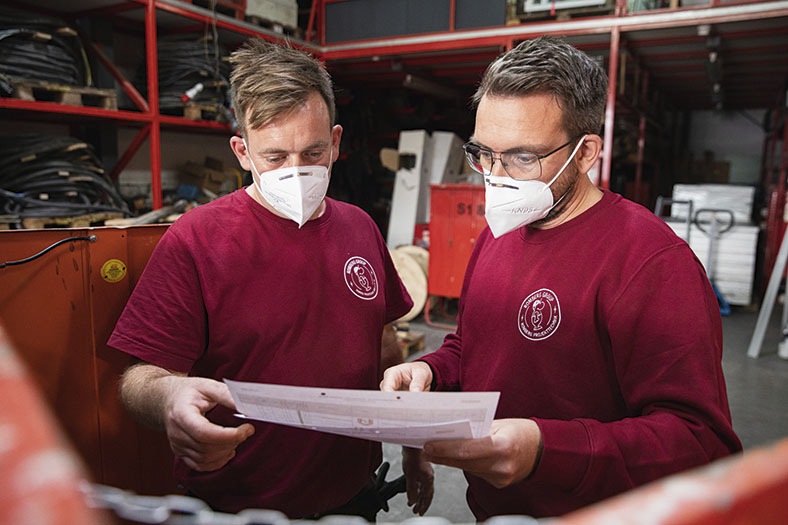 Zwei Männer, in rotem T-Shirt und rotem Sweatshirt mit weißem Firmenlogo stehen nebeneinander in einem Lagerraum und schauen zusammen auf Papiere. Beide tragen eine weiße FFP2-Maske. Der Mann rechts trägt eine Brille und einen dunklen Vollbart.
