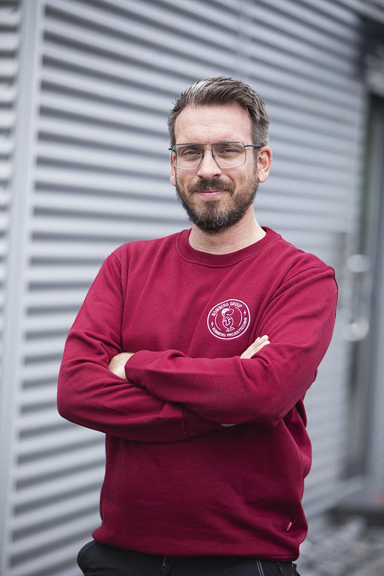 Das Portrait zeigt Christian Schnell von der Romberg Group. Er hat kurze, dunkle Haare, einen Vollbart und trägt ein rotes Sweatshirt mit Firmenlogo. Er steht vor einer Wellblechwand und schaut mit verschränkten Armen lächelnd in die Kamera.