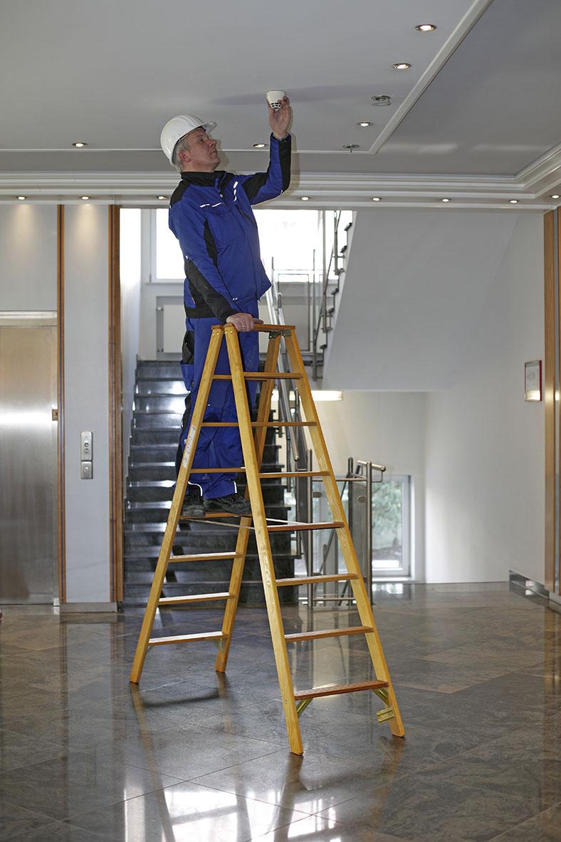 Auf dem Bild steht ein Arbeiter auf einer Klappleiter aus Holz. Er hat graue Haare, trägt blau-schwarze Arbeitskleidung und einen weißen Helm. Er befestigt eine weiße Dose an der Decke eines Treppenhauses.