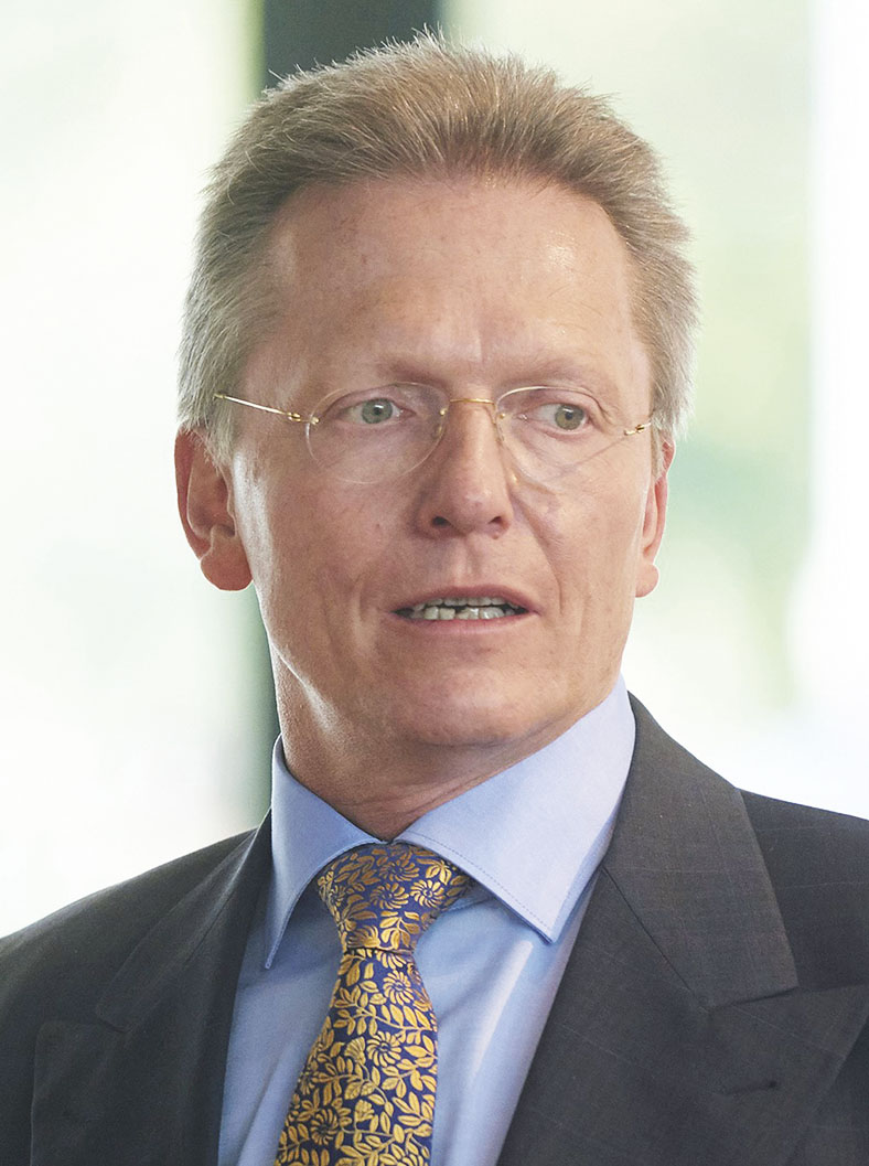 Portraitfoto von Dr. Reinhard Lux, BG ETEM. Er hat kurze blonde Haare, trägt eine Brille und einen Anzug.