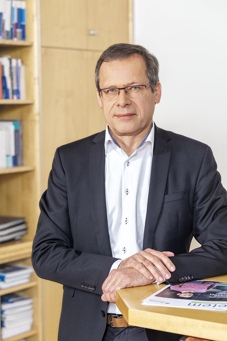 Porträtfoto von Johannes Tichi, Vorsitzender der Geschäftsführung der BG ETEM. Er hat kurze Haare und eine Brille. Er trägt ein dunkles Jackett, ein weißes Hemd und stützt einen Arm auf einen Stehtisch, auf der die neue Ausgabe des etem-Magazins liegt.