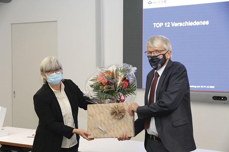 Das Foto zeigt links Karin Jung und rechts Dr. Heinz-Willi Mölders. Sie halen zwischen sich einen Blumenstrauß und ein verpacktes Geschenk. Frau Jung hat kürzere graue Haare, trägt eine Brille und einen blauen Mund-Nasen-Schutz, eine helle Bluse und einen schwarzen Blazer, Dr. Mölders hat graue Haare, trägt eine Brille sowie einen schwarz-grauen Mund-Nasen-Schutz, einen grauen Anzug mit roter Krawatte und hellem Hemd.