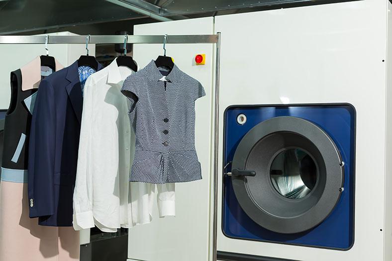 Rechts eine industrielle Waschmaschine, rechts eine Kleiderstange, an der verschiedene Kleidungsstücke an Kleiderbügeln hängen.