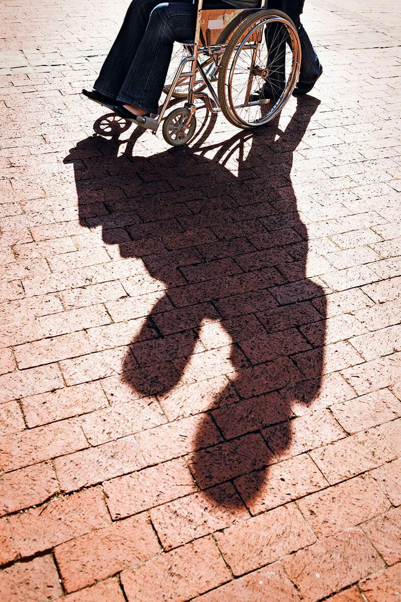Das Foto zeigt den unteren Teil einer Rollstuhlfahrerin, die von einem Mann angeschoben wird. Im Vordergrund ist der Schatten der Rollstuhlfahrerin und des anschiebenden Mannes zu erkennen.