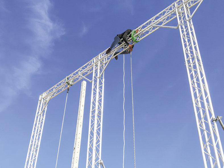 Dieses Foto zeigt einen Höhenarbeiter (Rigger) beim Aufbau einer Traverse.