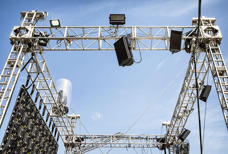 Das Foto zeigt eine Bühnenkonstruktion, bei der Scheinwerfer und Lautsprecher angebracht sind.
