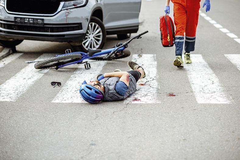 Das Foto zeigt einen verletzten Radfahrer mit Schutzhelm, der auf einem Zebrastreifen liegt. Er blutet am Arm. Blutflecke sind ebenfalls auf dem Zebrastreifen. Vor ihm das Vorderrad seines Fahrrads.