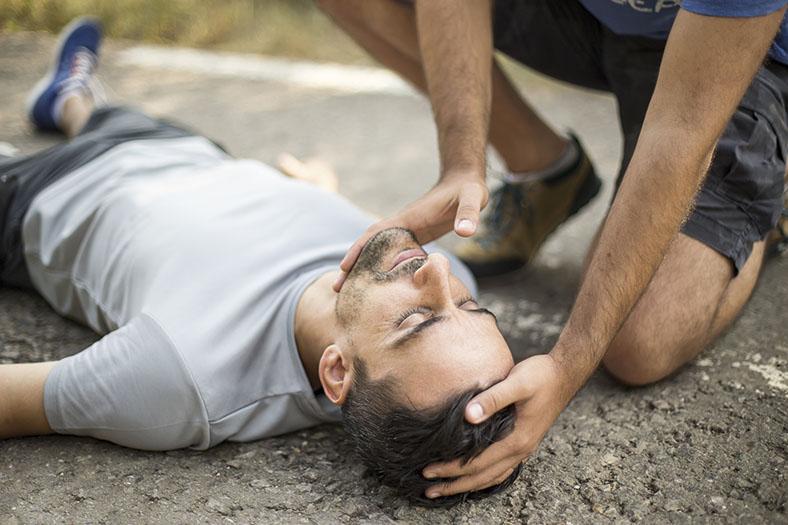 Dieses Bild zeigt einen Mann, der am Boden liegt. Ein Ersthelfer positioniert den Kopf des Verletzten mit beiden Händen in die richtige Richtung.