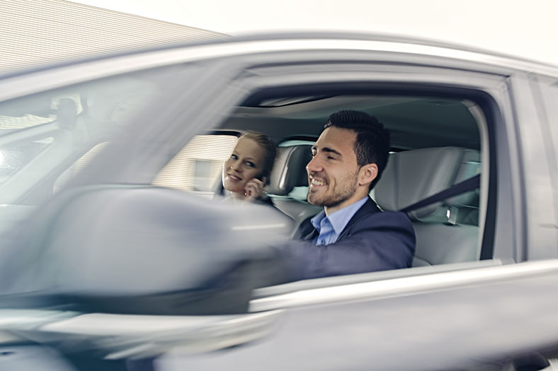 Ein Mann sitzt bei geöffnetem Fenster in einem Pkw. Eine Frau sitzt auf dem Beifahrersitz und lächelt.