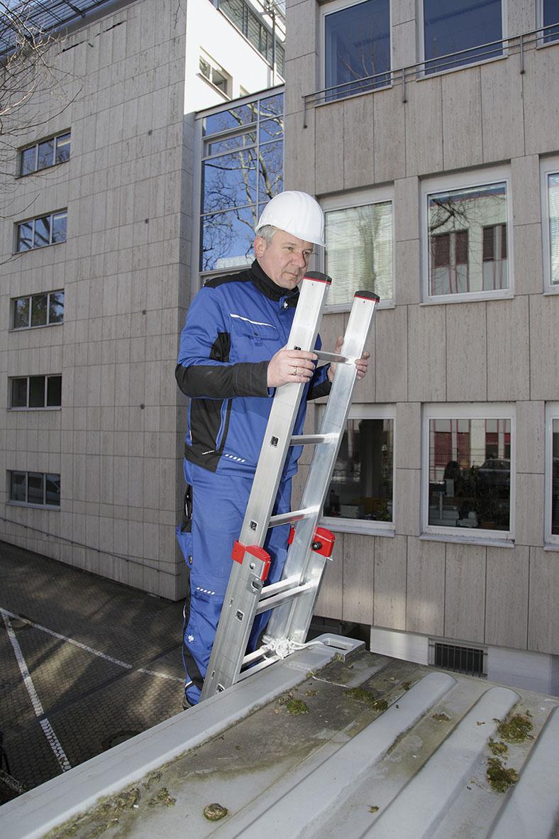 Dieser Arbeiter mit Schutzhelm und Schutzkleidung ist auf einer Leiter hochgeklettert und ist auf dem Dach eines Containers angekommen.