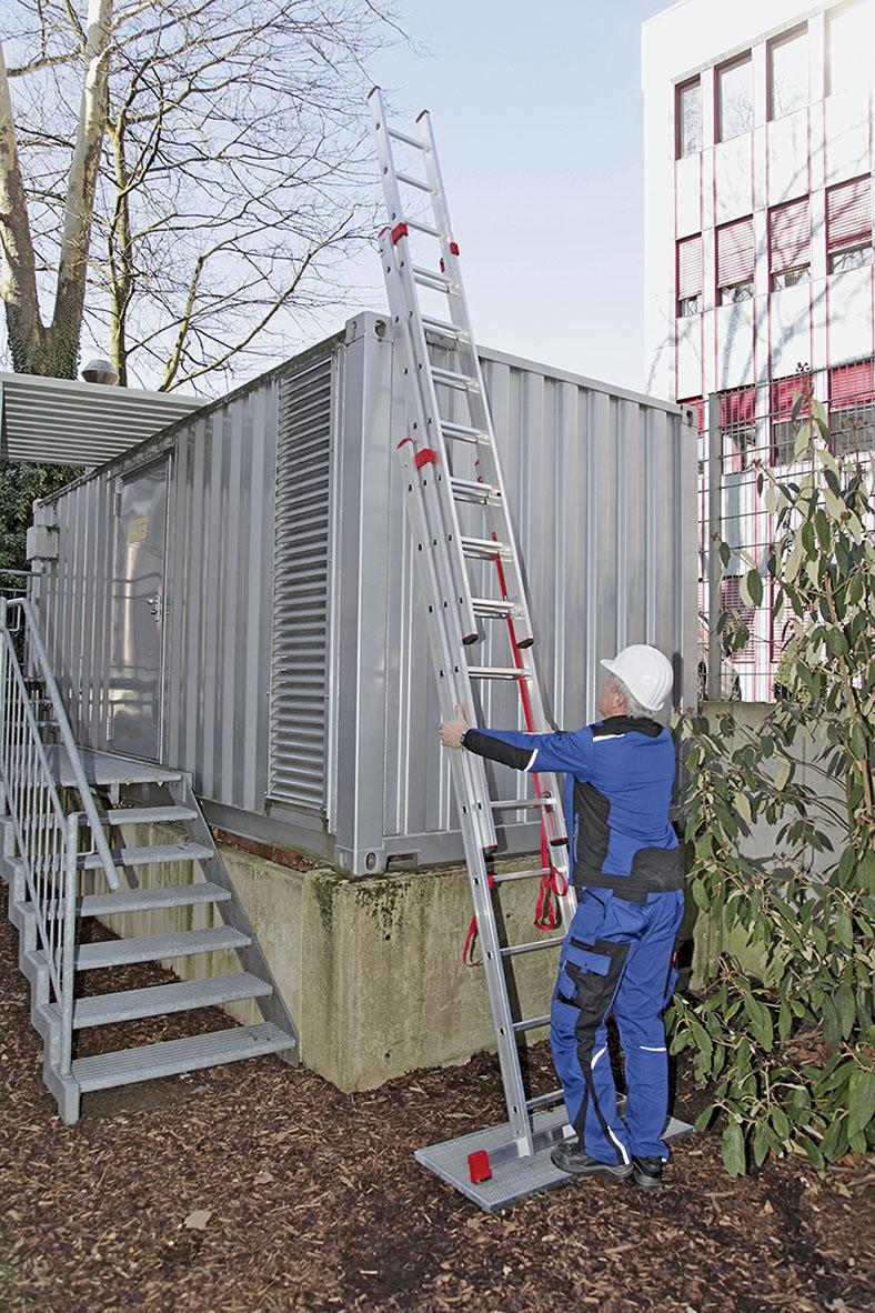 Das Foto zeigt einen Arbeiter mit Schutzhelm und Schutzkleidung. Er hält mit beiden Händen eine Aluminiumleiter fest, mit der er an einem Container hochklettern möchte.