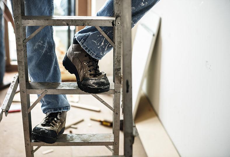 Das Bild zeigt eine Person, die eine Holzleiter hinaufklettert. Es werden nur die Beine gezeigt, die mit Jeans und Schuhen bekleidet sind.