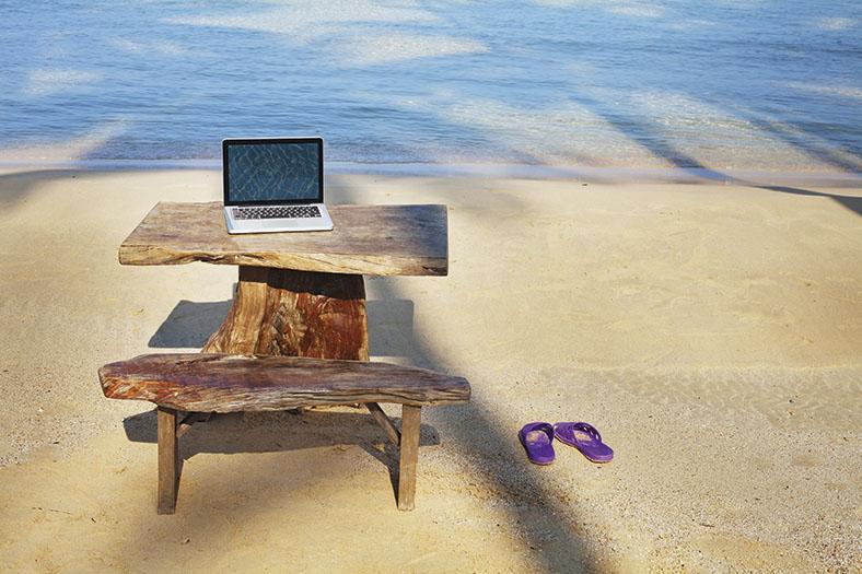 Dieses Foto zeigt einen Holztisch auf dem ein Laptop steht. Davor steht eine Holzbank und daneben ein paar lila Badeschuhe. Im Hintergrund erkennt man das Meer.