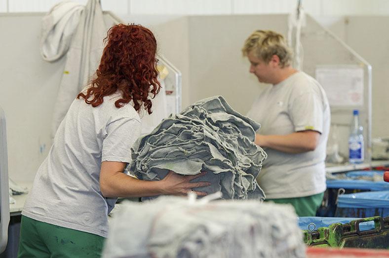 Das Foto zeigt eine Mitarbeiterin im Vordergrund, vor ihr ein Stapel Putztücher, die manuell kontrolliert werden müssen. Im Hintergrund ist noch eine andere Mitarbeiterin mit derselben Tätigkeit beschäftigt.