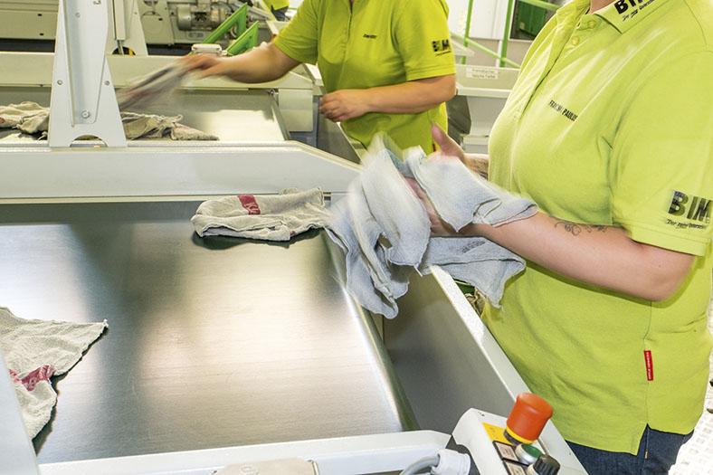 Diese Abbildung zeigt zwei Mitarbeiterinnen an der neuen Anlage. Die Qualitätskontrolle wird noch von den Beschäftigten erledigt.