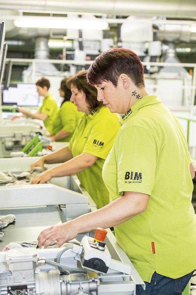 Dieses Foto zeigt Mitarbeiterinnen während ihrer Tätigkeit an einer modernen Sortieranlage für gereinigte Putztücher.