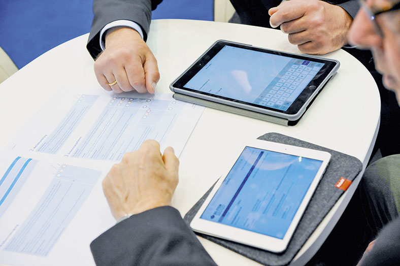 Das Foto zeigt einen Tisch, wo zwei Tablets und eine Unterlage liegen. Auf der rechten Seite erkennt man das Profil eines Messebesuchers, der an diesem Tisch sitzt.