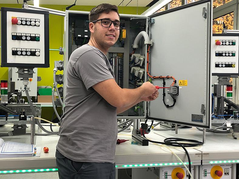 Das Bild zeigt eine jungen Mann in grauem T-Shirt mit Brille. Er steht mit einem Schraubenzieher vor einem offenen Elektrogerät, das auf einem Tisch steht. Die Tischkante ist mit einer grünen LED-Leiste versehen.