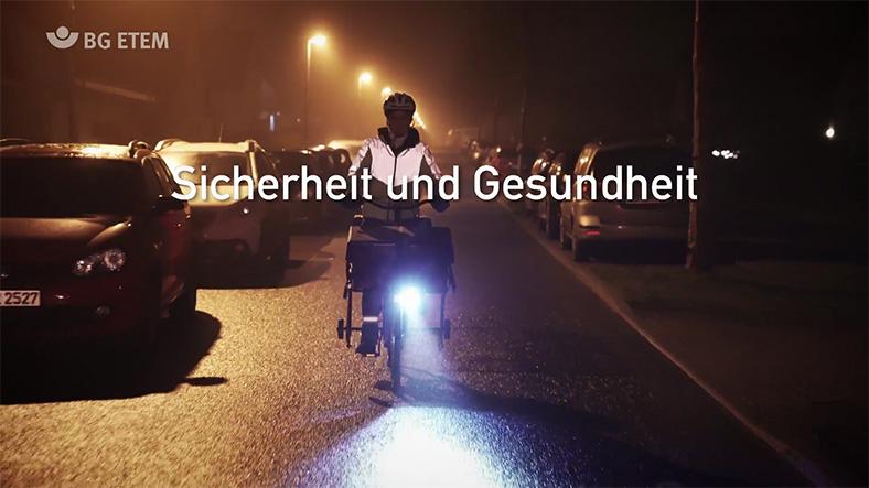 Auf dem Bild sieht man eine nächtliche Straße, auf der eine Zeitungszustellerin mit einem blauen Fahrrad fährt. Über dem Bild steht in weißer Schrift: Sicherheit und Gesundheit.