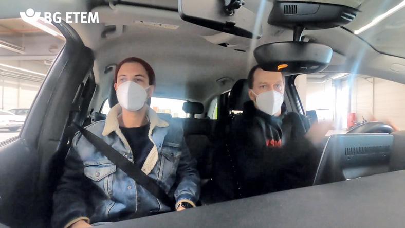 Das Bild zeigt den Innenraum eines Pkw mit zwei Personen, die beide einen weißen Mundschutz tragen. Der Fahrer testet seine Reaktionen unter Alkoholeinfluss.