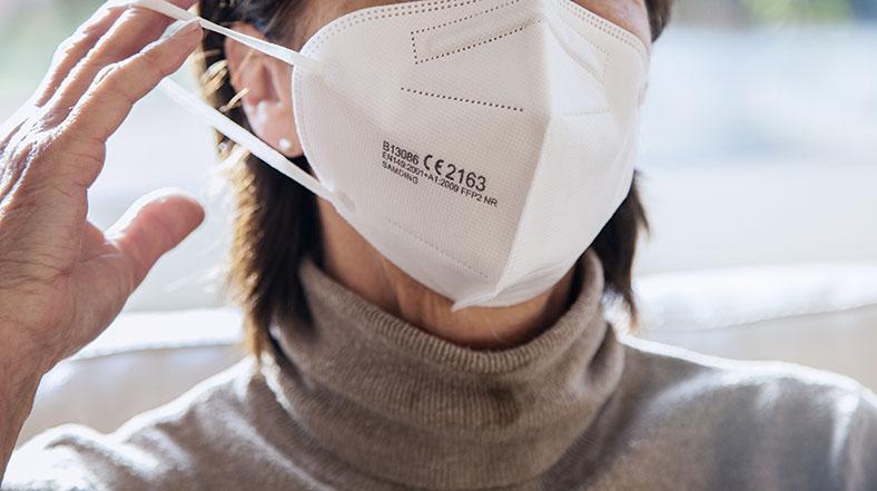 Bildausschnitt einer weiblichen Person, die sich eine FFP2-Maske fachgerecht aufsetzt. Sie trägt kurzes, braunes Haar und einen hellbraunen Rollkragenpullover.
