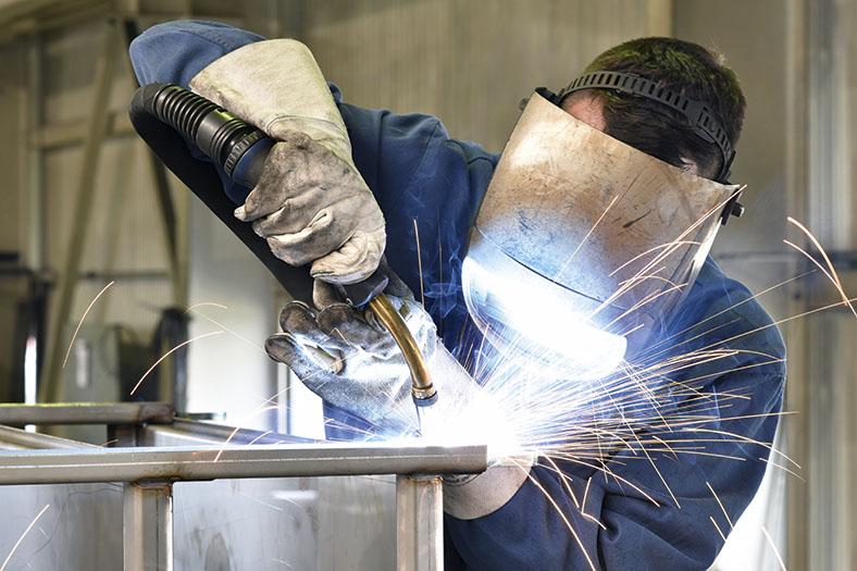 Ein Metallbau-Beschäftigter in Schutzausrüstung schweißt Metallteile zusammen.
