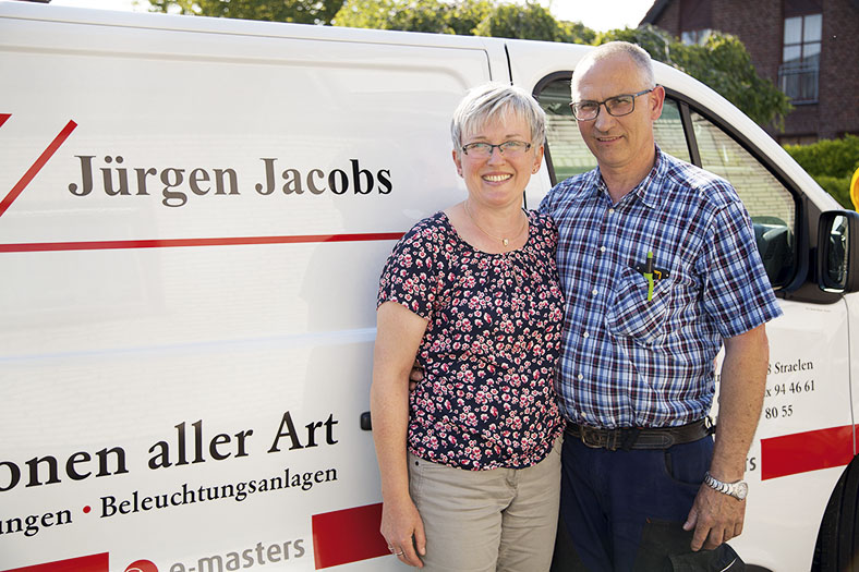 Das Bild zeigt das Ehepaar Petra und Jürgen Jacobs in Halbansicht. Sie stehen dicht nebeneinander vor ihrem weißen Firmenwagen in der Sonne und lächeln in die Kamera. Beide haben kurze graue Haare und tragen eine Brille sowie kurzärmelige Oberteile.