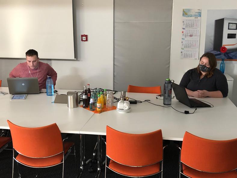 Mario Häuberer und Jana Nissel sitzen mit Abstand an einem hellen Konferenztisch vor ihren Notebooks bei einer Arbeitsschutzunterweisung. Frau Nissel - rechts im Bild - hat dunkle Haare, trägt einen Mund-Nasen-Schutz und ein dunkles Oberteil. Herr Häuberer - links im Bild - hat kurze dunkle Haare und trägt ein rotes Oberteil. Auf dem Tisch stehen Getränke, im Vordergrund sieht man rote Stühle.