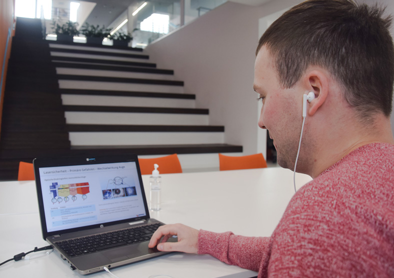 Ein Mann mit kurzen braunen Haaren und rotem Shirt sitzt im Betrieb vor einem Notebook, auf dem Bildschirm sieht man Details zu einer digitalen Arbeitsschutzunterweisung. Er trägt ein Headset, das mit dem Notebook verbunden ist. Im Hintergrund ist eine Treppe zu sehen.