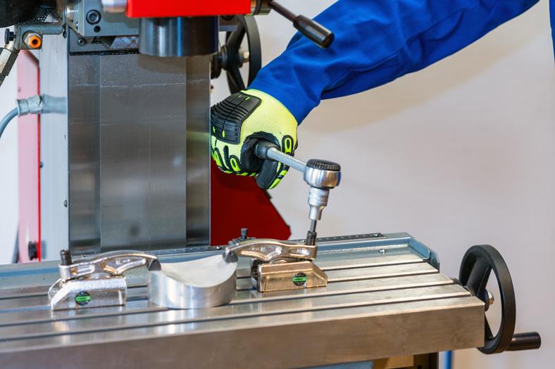 Die Hand eines Arbeiters in gelb-schwarzem Schutzhandschuh zieht eine Schraube an einer Maschine fest.