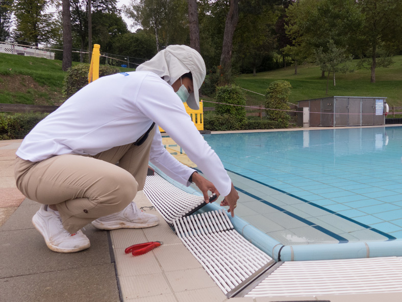 Ein Handwerker arbeitet an der Umrandung eines Freischwimmbeckens. Zum Schutz vor Sonneneinstrahlung trägt er helle, lange Kleidung und eine Kappe mit Nackenschutz sowie einen Mund-Nasen-Schutz.