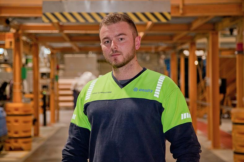 Porträt eines Mannes mit blonden Haaren und Vollbart in einer Werkshalle mit orangen Metallstreben. Er trägt ein schwarz-gelbes Shirt mit Logo essity und schaut in die Kamera.