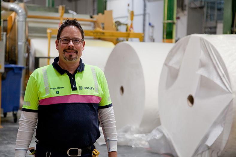 Ein Mann steht in einer Lagerhalle, rechts im Hintergrund große Papierrollen. Er hat kurze, dunkel Haare, einen Vollbart, trägt eine Brille und ein schwarz-gelbes Shirt mit dem Firmenlogo von essity. Er lächelt in die Kamera.