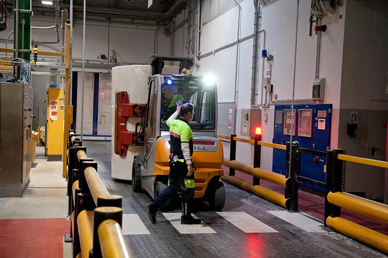 Das Bild zeigt eine Produktionshalle: Ein Fußgänger überquert eine Fahrbahn auf einem Zebrastreifen, während ein Transportfahrzeug wartet.