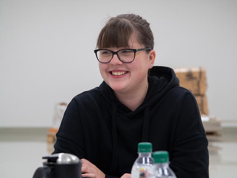 Das Bild zeigt das Porträt einer lächelnden Jugendlichen mit Brille. Ihre dunklen Haare sind zurückgebunden. Sie sitzt an einem Tisch, vor ihr sind Getränkeflaschen und eine Kaffeekanne teilweise sichtbar.