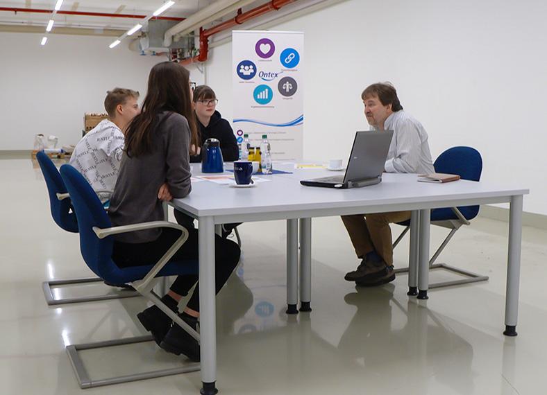 In einem fensterlosen Raum mit Leitungen an der Decke sitzen mehrere Jugendliche und ein Erwachsener um einen Tisch. Auf dem Tisch steht ein Aufsteller mit bunten Symbolen.