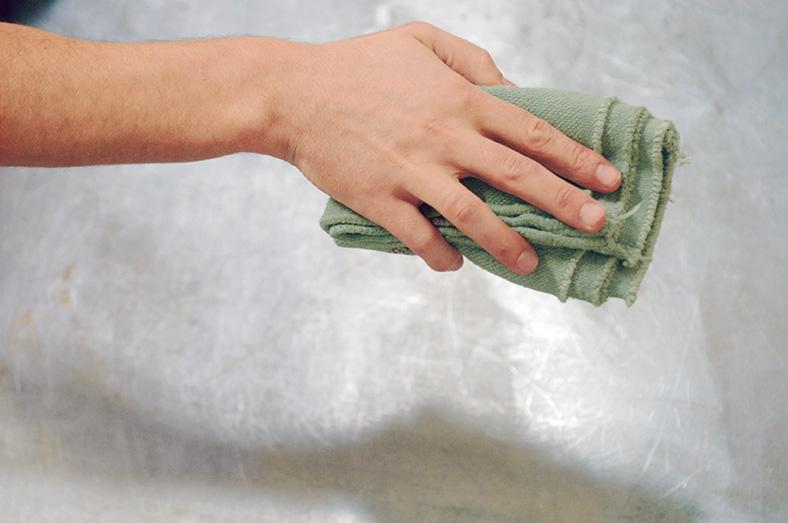 Das Bild zeigt eine Hand, die ein Putztuch hält.