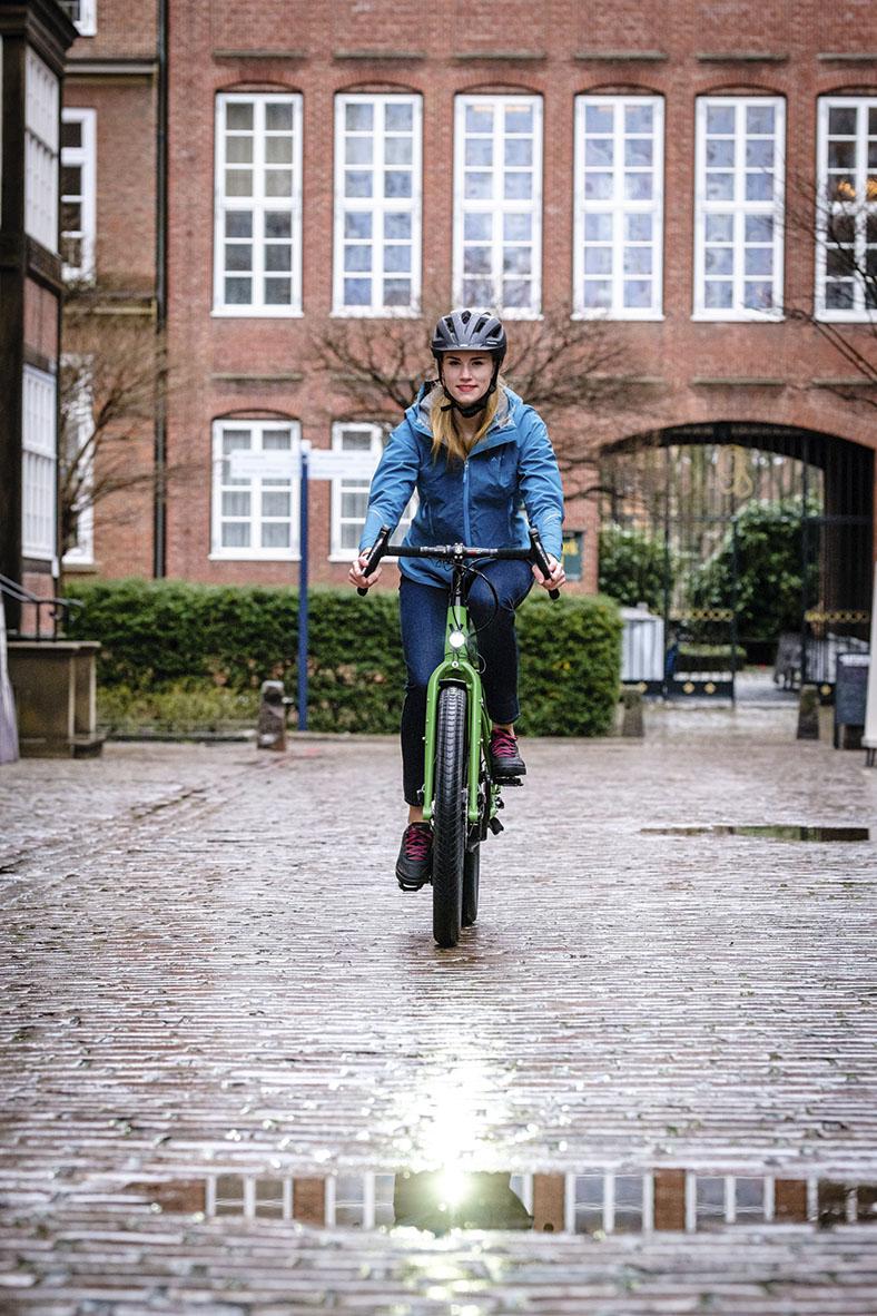 Frontalansicht einer Radfahrerin mit dunklem Schutzhelm und blauer Jacke auf einem grünen Fahrrad. Im Hintergrund ein roter Backsteinziegelbau mit weißen Sprossenfenstern.