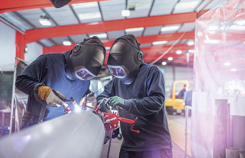 Zwei Arbeiter in Schweißer-Schutzkleidung mit Handschuhen und komplettem Gesichtsschutz stehen in einer Fabrikhalle und schweißen an einem Rohr.