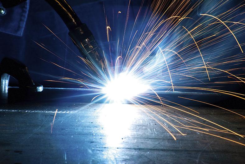 Lichtbogen beim Schweißen einer Stahlkomponente vor dunklem Hintergrund mit sprühenden Funken.